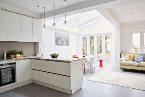 White fitted kitchen, lounge and dining area in modern open-plan interior with terrace view
