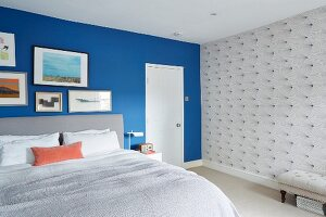 Gallery of pictures on blue wall and wallpaper with graphic patter in bedroom