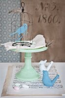 Hand-made wire birdcage and bird figurine, cake stand, sheet music and bird whistles