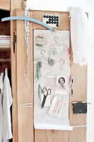 Various sewing accessories and hand-made wire coathangers hung on cupboard door