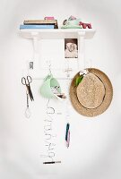 Various accessories hung from hooks below white wall-mounted bracket shelf