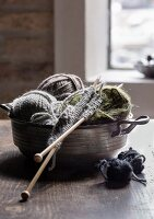 Knitting work and balls of wall in pewter bowl
