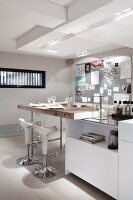 White island counter with solid wooden countertop and designer bar stools