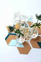 Vases of thistles and gypsophila on hand-made, hexagonal, painted cork coasters
