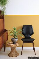 Yucca on wicker stool next to black retro chair