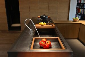 Modern, metal counter with integrated wooden chopping board and gas hob in front of simple fitted cupboards
