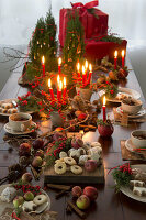Christmas table decorated with candles, biscuits, holly, apples and apple tea