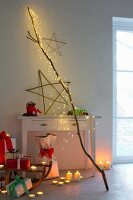 Atmospheric Christmas arrangement: cascade of LED lights on branch, willow star, tealights, candles and gifts
