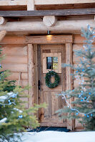 Wreath on wooden door of rustic log cabin in winter