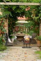 Autumnal seating area with climber-covered pergola and fire basket