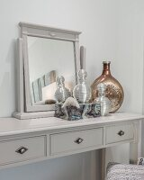 Mirror and elegant perfume bottles on grey dressing table