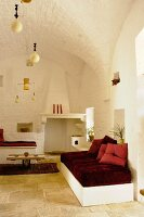 Whitewashed lounge with red accents and vaulted ceiling in renovated trullo