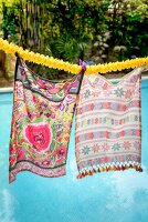 Brightly patterned scarves hanging from garland of flowers above pool