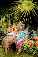 Colourful rug and ornaments on wooden elephant in exotic garden