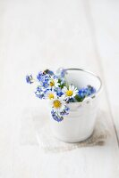 Forget-me-nots and daisies in small ceramic bucket