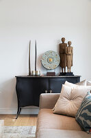 Sculptures on antique cabinet and sand-coloured couch with scatter cushions in foreground