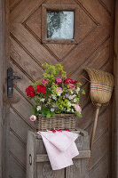 Bouquet of roses and lady's mantle in basket in front of front door