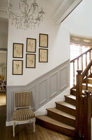 Chair at foot of staircase with panelled wainscotting and gallery of botanical illustrations