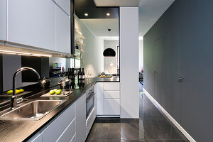 Brightly lit kitchen with grey walls and serving hatch