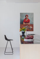 Black bar stool at kitchen island below portrait of woman on wall