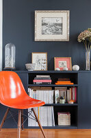 Orange designer chair in front of half-height shelves against grey wall