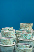 Turquoise-glazed pots with structured surfaces against blue wall