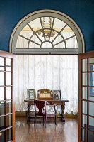 View of antique desk through double lattice doors with fanlight