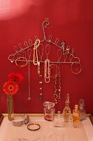 Coat hanger covered in loops of wire used as jewellery rack on red wall