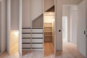 Walk-in wardrobes with open doors and lighting