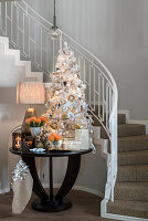 White Christmas tree and festive decorations on table at foot of staircase