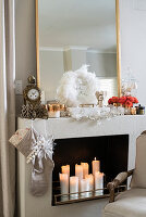 Lit candles in festively decorated false fireplace