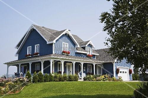 idyllisches pastellblaues haus mit veranda und gepflegtem garten bild kaufen living4media. Black Bedroom Furniture Sets. Home Design Ideas