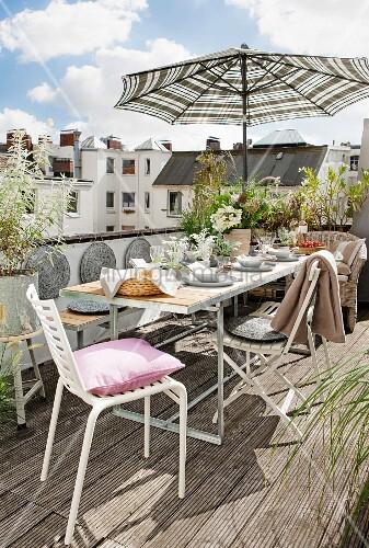 gedeckter tisch mit st hlen und sonnenschirm auf dem balkon bild kaufen living4media. Black Bedroom Furniture Sets. Home Design Ideas