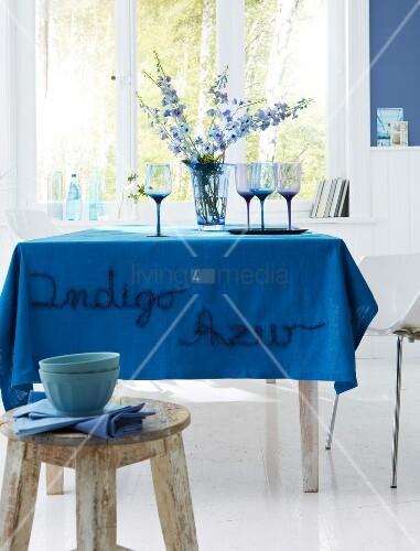 tisch mit azurblauer bestickter tischdecke bild kaufen living4media. Black Bedroom Furniture Sets. Home Design Ideas