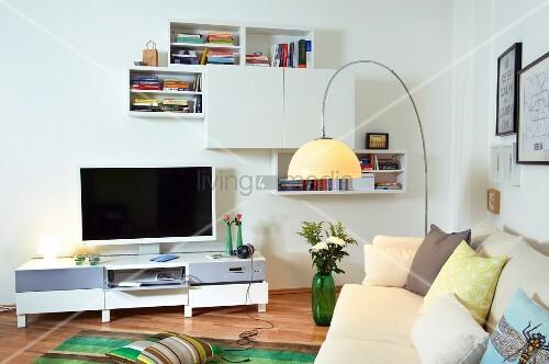 h ngeregale ber medienm bel mit fernseher und cremefarbenes sofa mit zierkissen im vordergrund. Black Bedroom Furniture Sets. Home Design Ideas