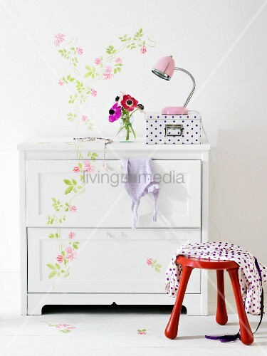 White chest of drawers with floral detail continuing onto white wall