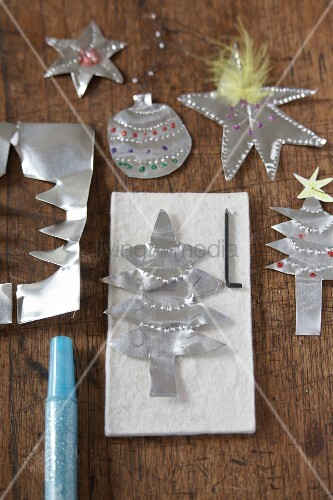 christmas tree decorations cut out of silver paper on