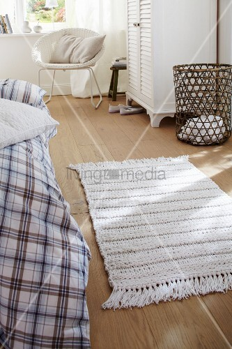 wei er gestrickter teppich auf holzdielen im schlafzimmer. Black Bedroom Furniture Sets. Home Design Ideas