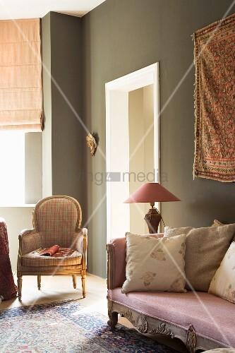 Antike Polstermöbel vor der graugrün getönten Wand eines ...