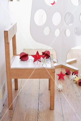 weihnachtsdeko auf einem kinderstuhl dahinter weisser weihnachtsbaum aus sperrholz bild. Black Bedroom Furniture Sets. Home Design Ideas