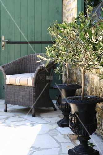 zwei blumenk bel und korbstuhl auf der terrasse eines. Black Bedroom Furniture Sets. Home Design Ideas