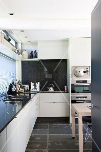 Blick in moderne Küche mit weissen Einbauschränken und schwarzem ...