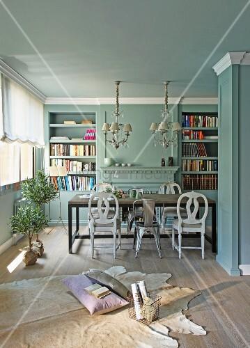 gem tlicher platz auf tierfell am boden vor esstisch mit verschiedenen st hlen in hellblau. Black Bedroom Furniture Sets. Home Design Ideas