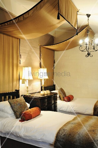 warme t ne im schlafzimmer baldachin aus goldbrauner seide ber betten aus dunklem. Black Bedroom Furniture Sets. Home Design Ideas