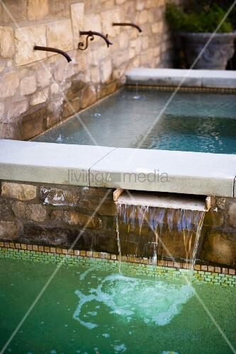 wasserfall aus naturstein brunnen in swimmingpool bild. Black Bedroom Furniture Sets. Home Design Ideas