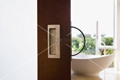 blick durch offene schiebet r aus holz auf freistehende badewanne bild kaufen living4media. Black Bedroom Furniture Sets. Home Design Ideas
