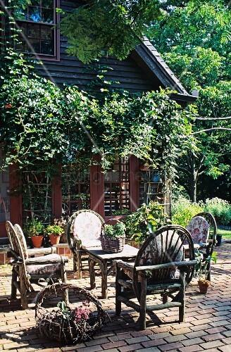 gepflasterte terrasse mit rustikalen holzm beln vor einem holzhaus mit wein pergola bild. Black Bedroom Furniture Sets. Home Design Ideas
