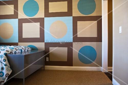 grafisch gemusterte wandgestaltung mit 70er jahre touch und farbig passender bettdecke hinter. Black Bedroom Furniture Sets. Home Design Ideas