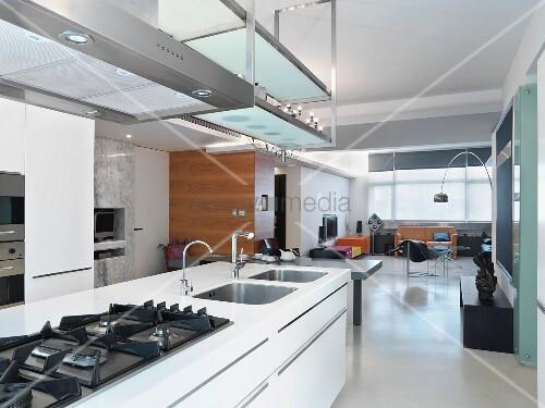 weisser freistehender k chenblock unter dunstabzug und h ngeregal von decke in offenem wohnraum. Black Bedroom Furniture Sets. Home Design Ideas