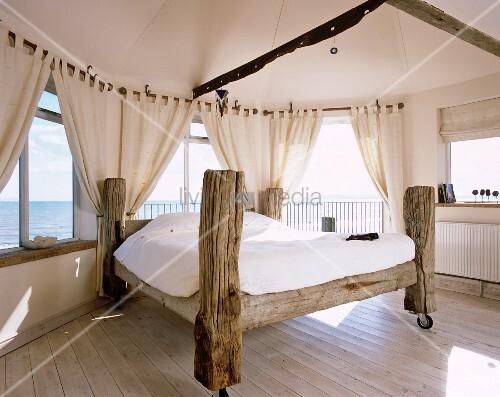 selbstgebautes bett aus baumst mmen und auf rollen im schlafzimmer mit panoramablick bild. Black Bedroom Furniture Sets. Home Design Ideas